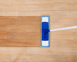 Overhead view of a modern sponge style mop being used for cleaning a wooden floor with copyspace